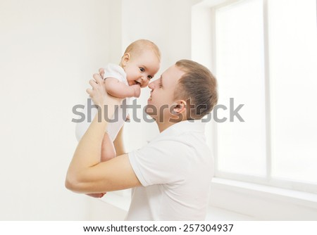 Happy father holding on hands his baby at home in white room  - stock photo