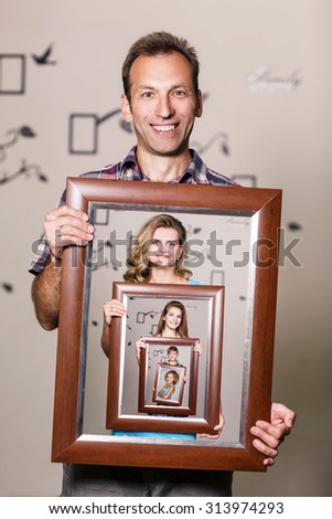 Happy father holding portrait with his family each is located inside their own frame  - stock photo
