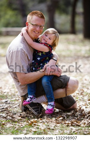 Happy father hugging his adorable toddler daughter - stock photo