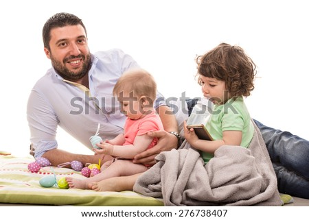 Happy father laying together with his baby daughter and toddler boy  - stock photo