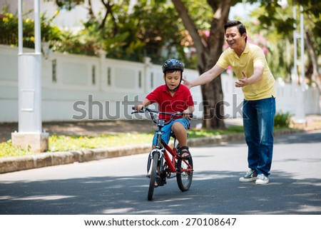 Happy father looking at his son riding a bike - stock photo