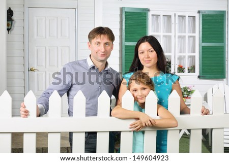 Happy father, mother and daughter stand next to white fence of their new cottage. - stock photo