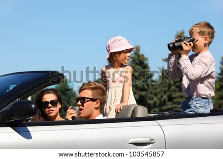 Happy father, mother and two children ride in convertible car and play; focus on man - stock photo