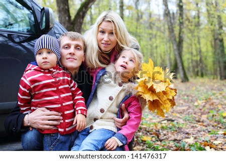 Happy father, mother, little son and daughter with yellow maple leaves near car in autumn forest. Focus on woman. Shallow depth of field. - stock photo