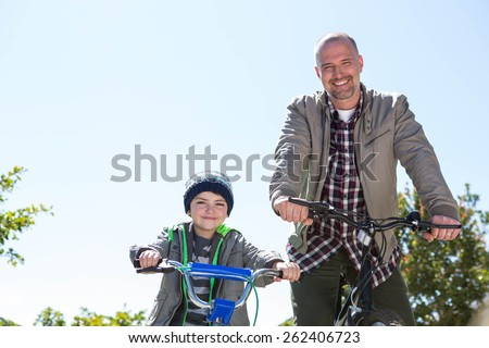 Happy father on a bike with his son on a sunny day - stock photo