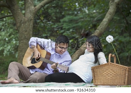 Happy father playing guitar for his unborn baby in the nature - stock photo