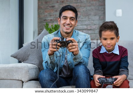 Happy father playing video games with his son in living room - stock photo