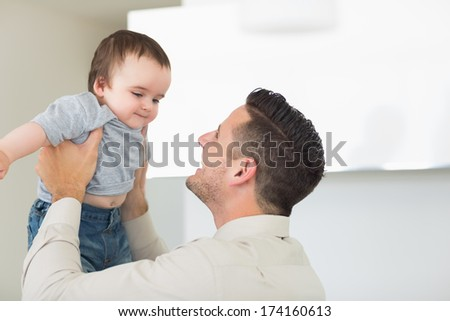 Happy father playing with cute baby boy at home - stock photo
