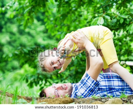 Happy father playing with his daughter in beautiful green grass - stock photo