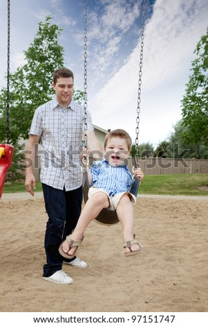Happy Father Pushing Boy On Swing In Playground. - stock photo