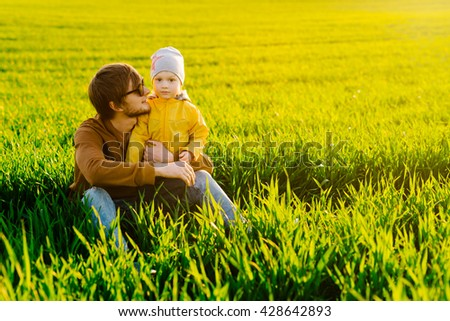 Happy father resting with his young son on summer field at sunset - stock photo