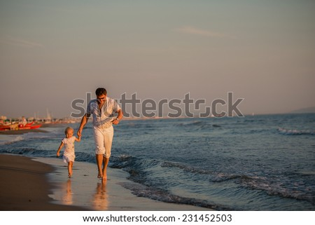 Happy father running with his daughter by the seaside at sunset, summer time. Fatherhood concepts, Italy, Forte dei Marmi - stock photo