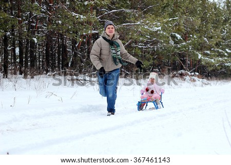 Happy father running with sledges on a winter day, little toddler girl in warm coat and knitted hat sitting on the sledge, family weekend outdoor - stock photo