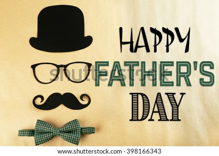 Happy Father's Day. Bowler hat, mustache and bow tie on beige background - stock photo