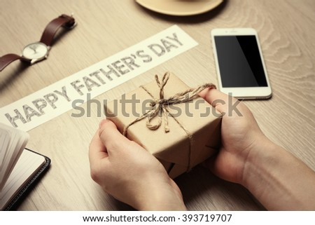 Happy Father's Day inscription with gifts and female hands on wooden background. Greetings and presents - stock photo