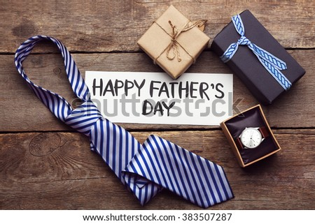 Happy Father's Day inscription with tie and watch on wooden background. Greetings and presents - stock photo