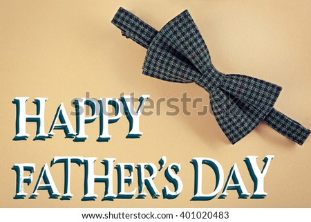 Happy Father's Day. Male bow tie on beige background - stock photo
