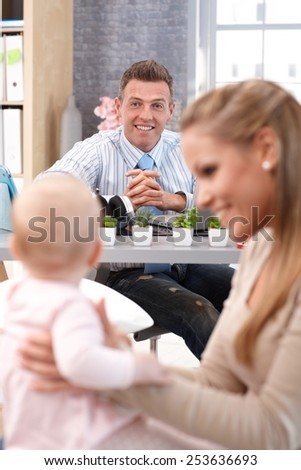 Happy father smiling at little daughter and wife from behind desk. - stock photo