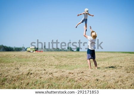 Happy father standing in middle of field tossing his son wearing hats shorts and T-shirts on summer day over blue sky background copyspace - stock photo