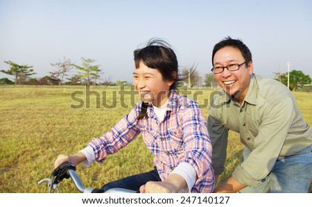 happy Father teaching child to ride bicycle - stock photo
