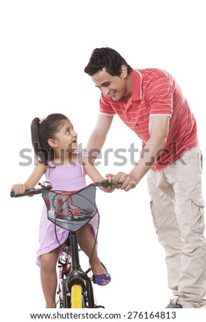 Happy father teaching daughter to ride bicycle against white background - stock photo