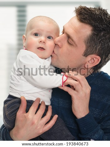 happy father with a baby on window background - stock photo