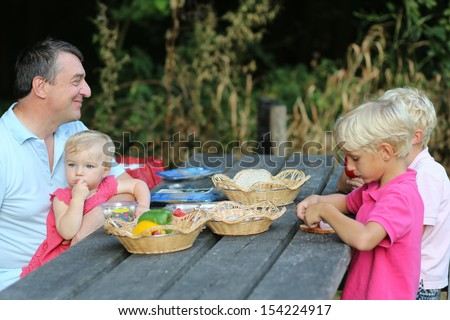 Happy father with children, 2 sons, teenager boys and little daughter, baby girl, are relaxing in the forest having picnic on a wooden table, eating healthy simple meal, vegetables, bread and fish - stock photo