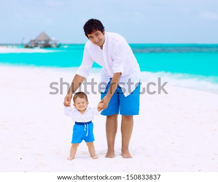 Happy father with cute baby on the beach, having tropical vacation - stock photo