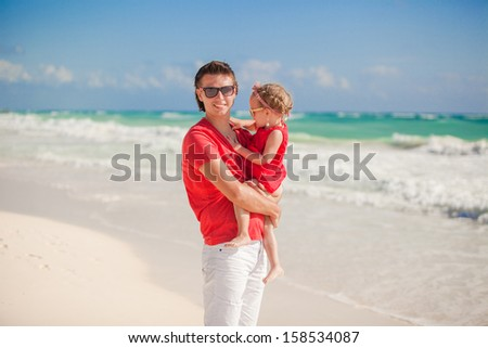 Happy father with cute daughter walking on tropical beach vacation - stock photo