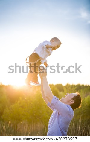 Happy father with his adorable toddler boy son on sunset. Father throwing cute baby in the sky on sunny day. Family having fun and enjoying day in the park. Fatherhood, childhood and lifestyle concept - stock photo