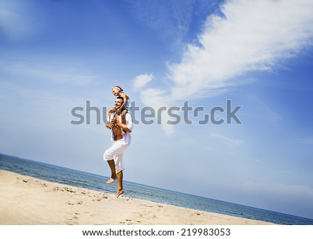 Happy father with his  little daughter at tropical beach having fun - stock photo