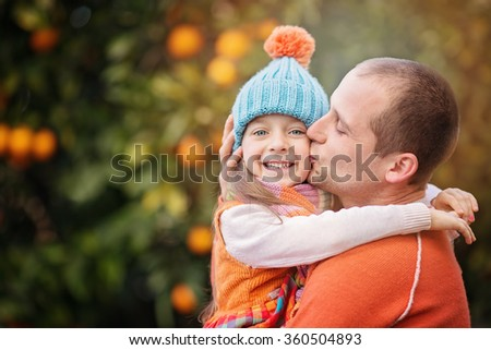Happy father with his little daughter having fun picking oranges.  - stock photo