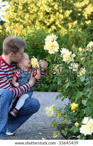 Happy father with his smiling daughter in the rose garden - stock photo