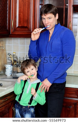 Happy father with his son brushing their teeth at home. - stock photo