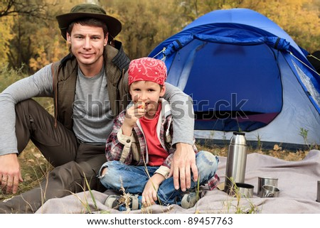 Happy father with his son having a rest outdoor in tent. - stock photo