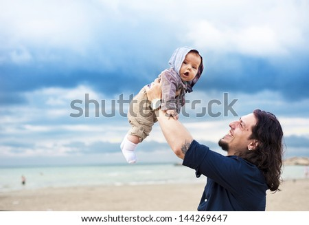 Happy father with newborn boy on the sea shore - stock photo