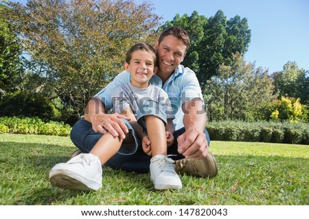 Happy father with son smiling at camera in a nice park in the sunshine - stock photo