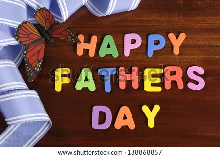 Happy Fathers Day childrens toy block colorful letters spelling greeting on dark rustic wood table with blue ribbon and butterfly. - stock photo