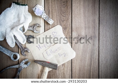 Happy Fathers Day with top border of tools and ties on a rustic wood background - stock photo