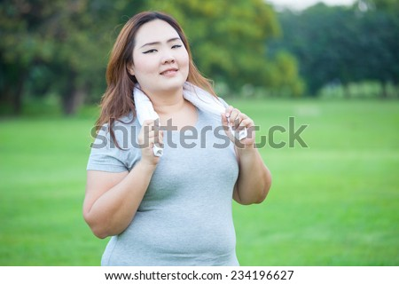 Happy fatty asian fit woman posing outdoor in a park - stock photo