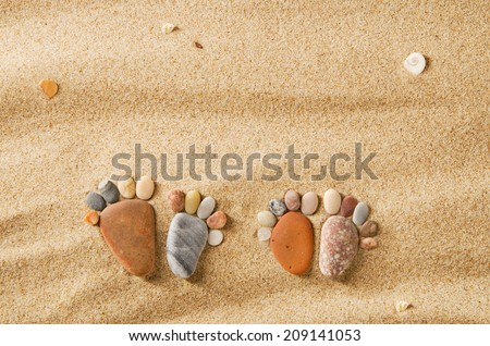 Happy feet. Stone arranged like a footprint on the beach - stock photo