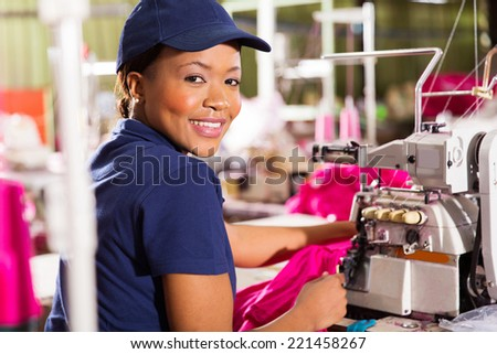 happy female african clothing factory worker sewing - stock photo
