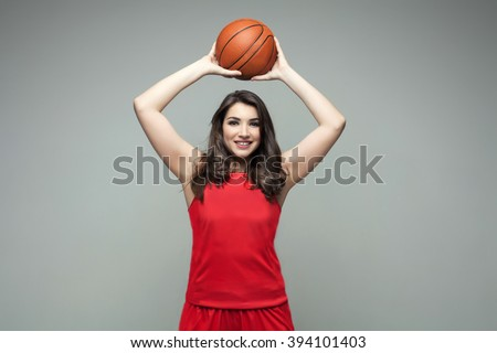 Happy female basketball player holding a ball - stock photo