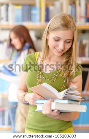 Happy female blonde student at library with books high school - stock photo