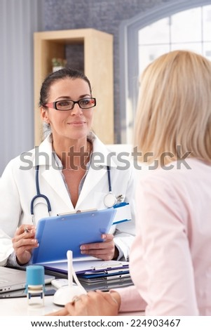 Happy female brunette doctor with glasses at medical office with patient, smiling, clipboard in hand, wearing stethoscope and lab coat. - stock photo