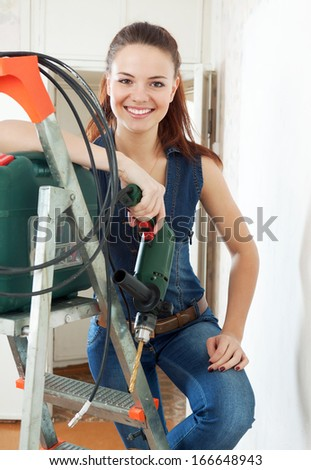Happy  female builder in overalls with tools and drill - stock photo