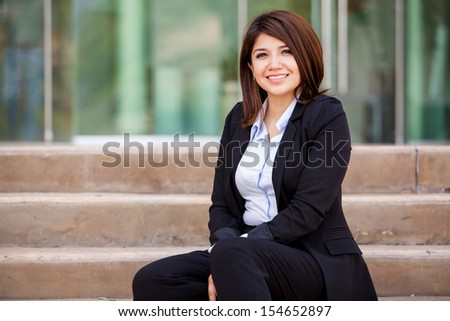 Happy female business school student sitting outside and relaxing - stock photo