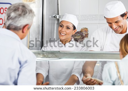 Happy female butcher looking at male customer in shop - stock photo