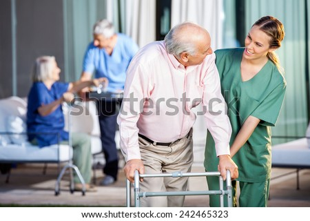 Happy female caretaker assisting senior man in using Zimmer frame at nursing home yard - stock photo