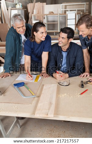 Happy female carpenter working on blueprint with team in workshop - stock photo
